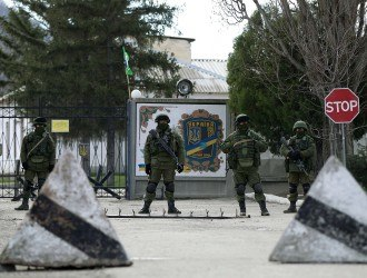 Armed men, believed to be Russians, stand guard near the Ukrainian military base in Perevalnoye outside Simferopol March 17, 2014. Ukraine's parliament, seeking to boost the country's military force in the face of Russia's takeover of the Crimea peninsula, endorsed a presidential decree on Monday to carry out a partial mobilisation involving 40,000 reservists. REUTERS/David Mdzinarishvili (UKRAINE - Tags: POLITICS CIVIL UNREST MILITARY)